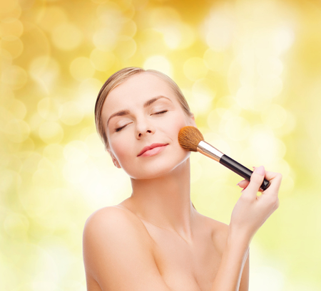 cosmetics, health and beauty concept - beautiful woman with closed eyes and makeup brush photo