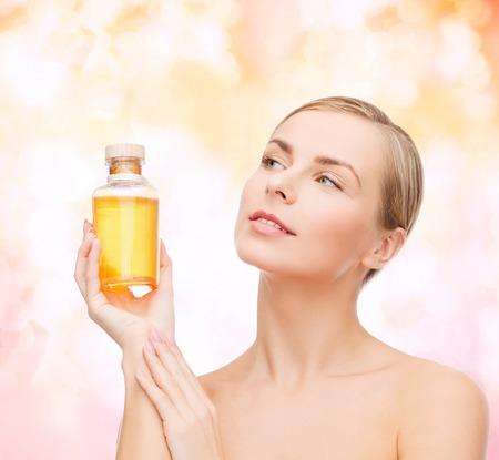 la salud, el spa y el concepto de belleza - mujer encantadora con la botella de aceite