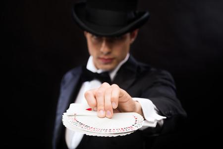 magia, performance, circo, juegos de azar, casino, poker, concepto de espectáculo - mago en la parte superior que muestra hat trick con naipes Foto de archivo