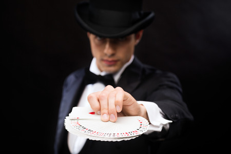 card game: magic, performance, circus, gambling, casino, poker, show concept - magician in top hat showing trick with playing cards Stock Photo