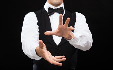 magic trick: magic, performance, circus, casino and show concept - casino dealer showing trick Stock Photo