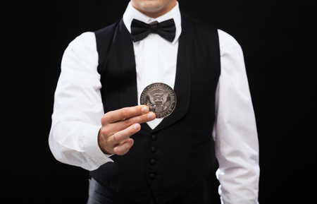 magic show: magic, performance, circus, casino and show concept - casino dealer holding half dollar coin Stock Photo