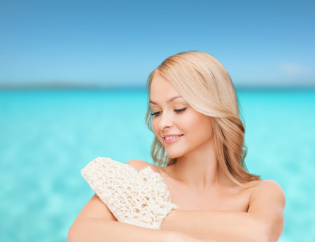 scincare: health, spa and beauty concept - smiling woman with exfoliation glove Stock Photo