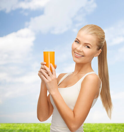 heath, diet and food concept - young woman holding glass of orange juice photo
