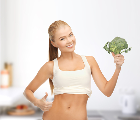 fat burning: health, diet and food concept - beautiful woman pointing at her abs and holding broccoli