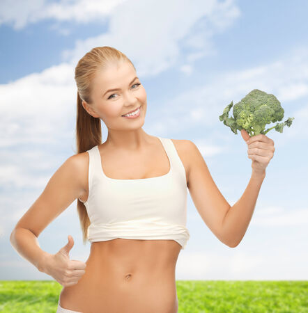 health, diet and food concept - beautiful woman pointing at her abs and holding broccoli photo