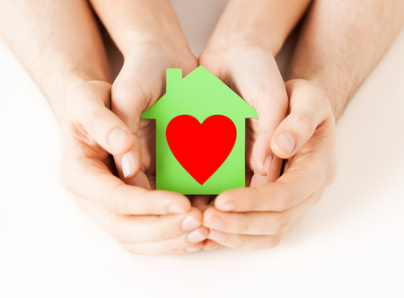 charity, real estate and family home concept - closeup picture of male and female hands holding green paper house with red heart photo