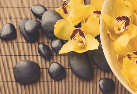 stone bowl: spa, heath and beauty concept - massage stones with orchid flowers on mat Stock Photo