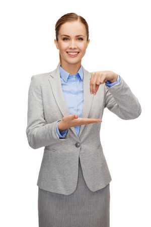 business, future technology and office concept - smiling businesswoman holding something imaginary photo
