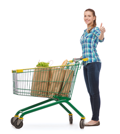 happiness, shopping and people concept - smiling young woman with shopping cart and food in it showing thumbs up Stock Photo - 26175216