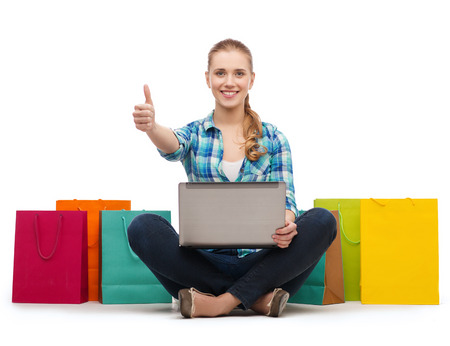 shopping, gesture, technology and internet concept - smiling girl with laptop computer and shopping bags over white showing thumbs up Stock Photo - 26175185