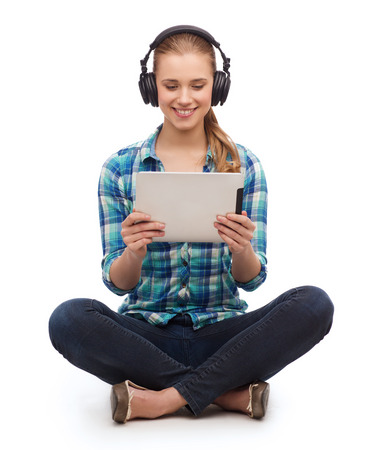 technology, internet and people concept - smiling young woman in casual clothes sitiing on floor with tablet pc computer and headphones photo