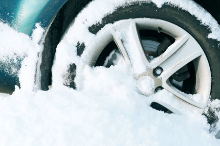 stuck: transportation, winter and vehicle concept - closeup of car wheel stuck in snow