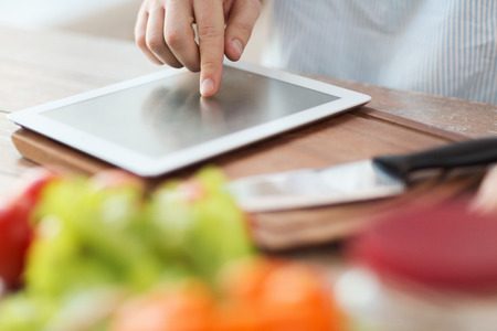 cooking, technology and home concept - closeup of man pointing finger to tablet pc computer Stock Photo