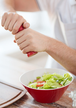 powder room: cooking and home concept - close up of male hands flavouring salad in a bowl Stock Photo