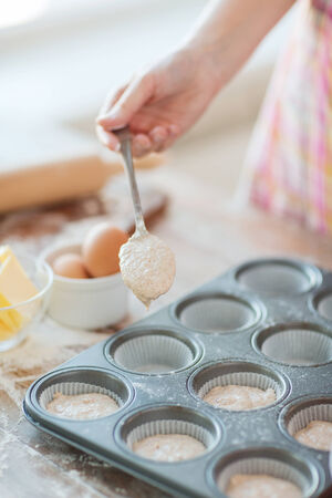 cooking and home concept - close up of hand filling muffins molds with dough photo