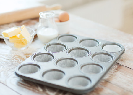 cooking and home concept - close up of empty muffins molds