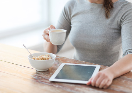 health, technology, internet, food and home concept - close up of woman drinking coffee and using tablet pc computer photo