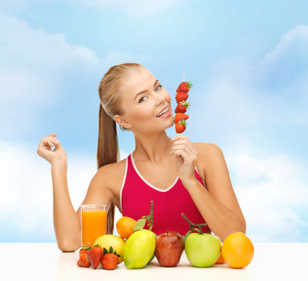 bodycare: fitness, diet and food concept - young woman with organic food or fruits eating strawberry Stock Photo