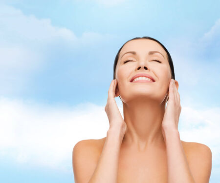 closed up: health, spa and beauty concept - clean face and hands of beautiful smiling woman with closed eyes Stock Photo