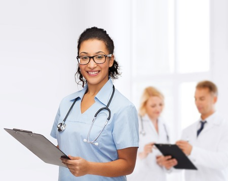 medical cabinet: healthcare and medicine concept - smiling female african american doctor or nurse in eyeglasses with stethoscope and clipboard Stock Photo