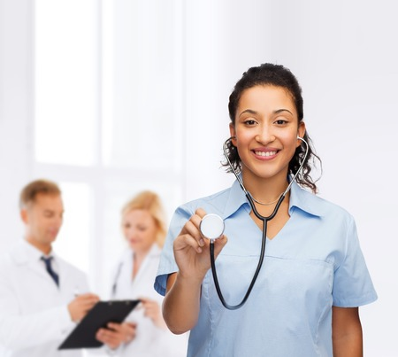 medical cabinet: healthcare and medicine concept - smiling female african american doctor or nurse with stethoscope