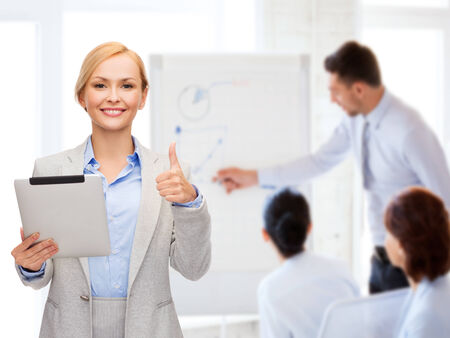 business, internet and technology concept - smiling woman with tablet pc computer showing thumbs up at office photo