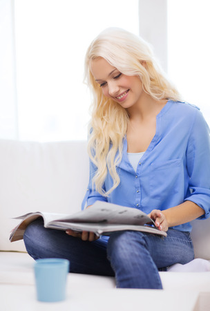home and leasure concept - smiling woman sitting on couch and reading magazine at home photo