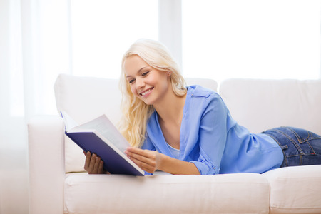 leasure: leasure and home concept - smiling woman reading book and lying on couch at home Stock Photo