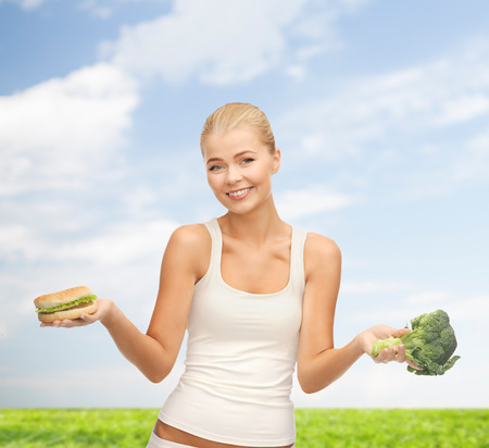 picture of sporty woman with broccoli and hamburger photo