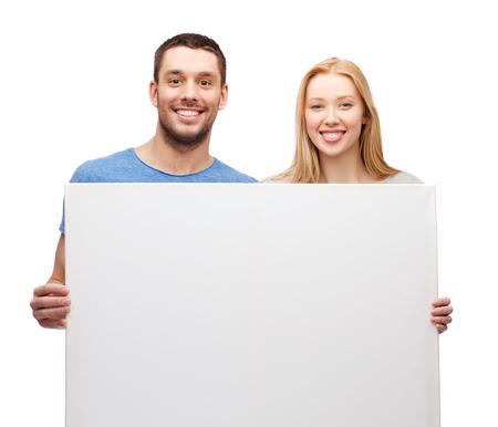 smiling couple holding white blank board photo