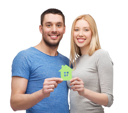 costruction: smiling couple holding green paper house Stock Photo