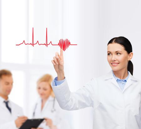 electrocardiograma: sonriente mujer médico que apunta al corazón y electrocardiograma