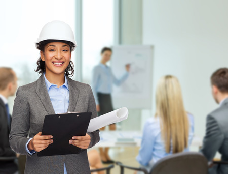 smiling businesswoman in white helmet with clipboard and blueprint at office photo