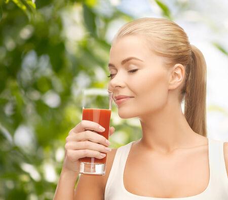 jugo verde: la salud, la dieta y el concepto de la comida - cerca de la mujer joven de beber jugo de tomate Foto de archivo