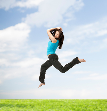 energetic people: picture of beautiful sporty woman jumping in sportswear Stock Photo