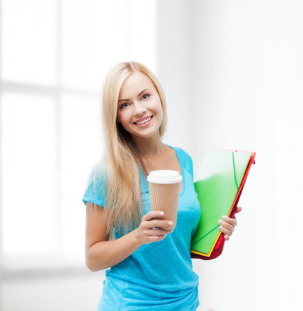 smiling student with folders and cup of coffee photo