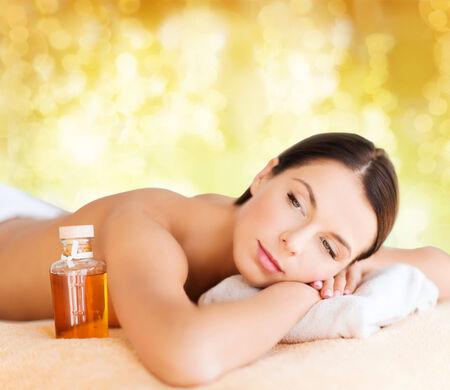 happy woman in spa salon lying on the massage desk photo