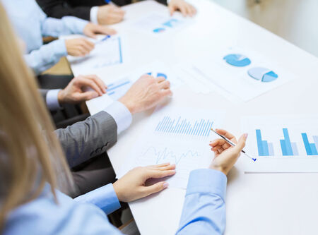 management meeting: close up of business team with chats and graphs in office