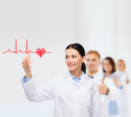 smiling female doctor pointing to heart and cardiogram Stock Photo