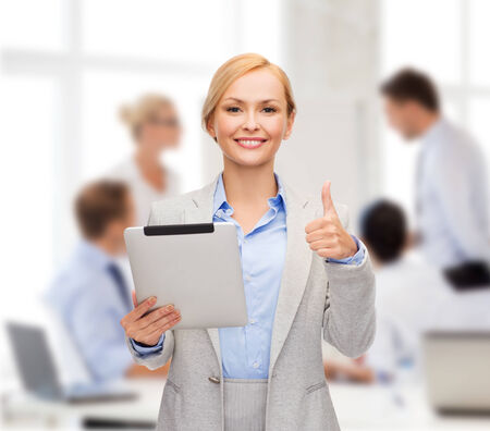 smiling woman with tablet pc computer showing thumbs up at office photo