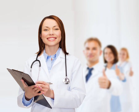 smiling female doctor with clipboard and stethoscope photo