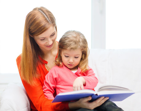 teaching children: family, children, pre-school and happy people concept - happy mother and daughter with book