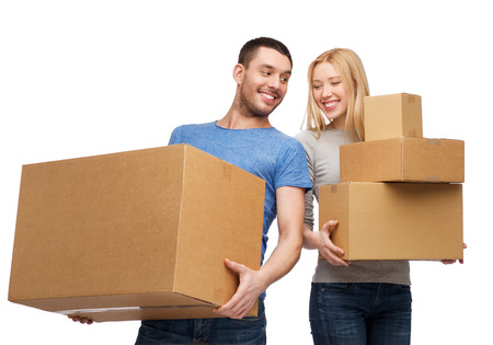 unwrapped: moving, home and family concept - smiling couple holding cardboard boxes