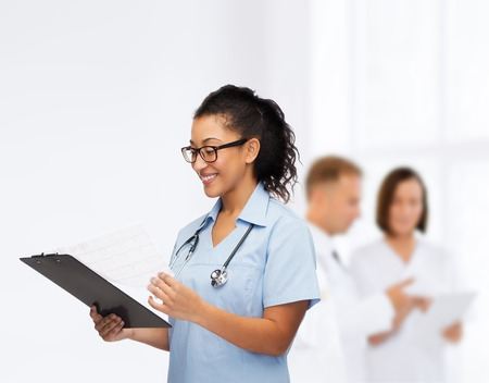 medical cabinet: smiling female african american doctor or nurse in eyeglasses with stethoscope and clipboard Stock Photo
