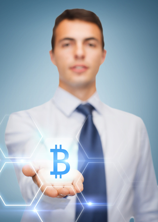 friendly young businessman showing bit coin sign on the palm of his hand photo
