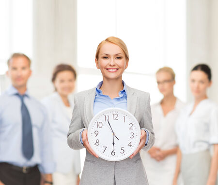 running out of time: attractive businesswoman with wall clock