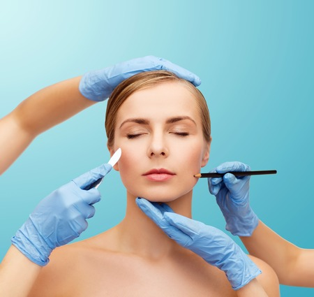 healthcare, beauty and medicine concept - beautiful woman face with closed eyes and beautician hands with pencil and scalpel photo