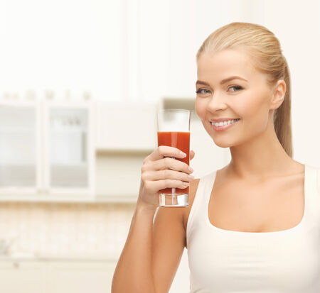 health, diet and food concept - young woman holding glass of tomato juice photo