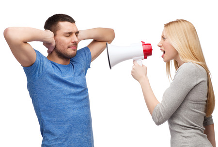 couple, family and relationship problems concept - girlfriend screaming though megaphone at his boyfriend photo